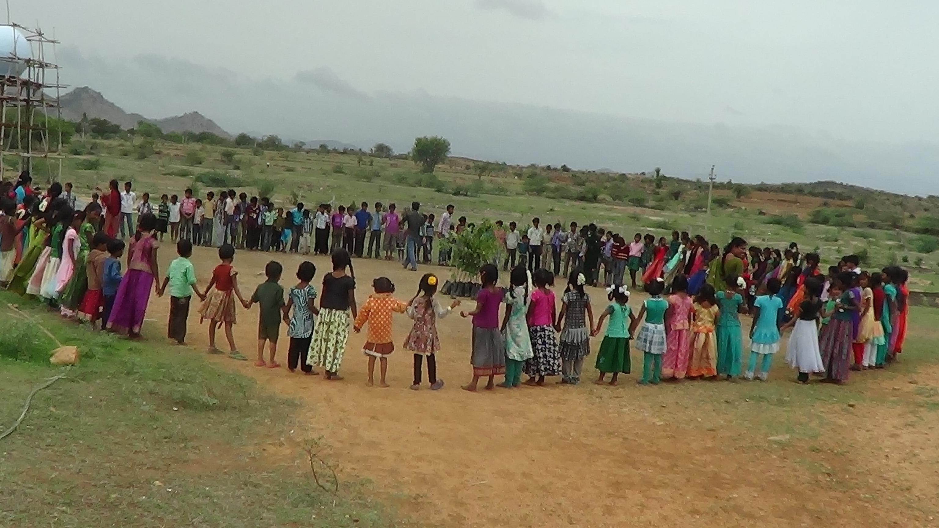 Students form a circle around some trees to be planted